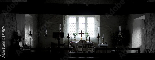 Fotografía Panoramic View Of Illuminated Candles With Cross On Altar Against Window At Chur