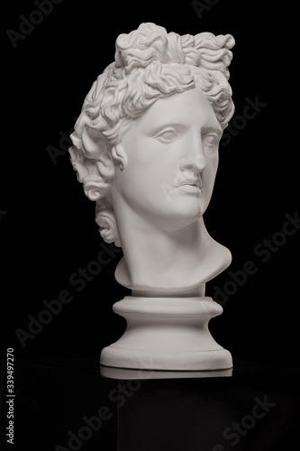 White plaster statue of a bust of Apollo Belvedere on a black background Fototapete