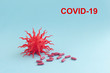 Covid-19 blue abstract background. Dangerous Coronavirus distribution model and hand. Pandemic COVID-19. Close up. Copy space