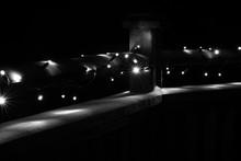Illuminated Christmas Lights On Railing With Snow At Night