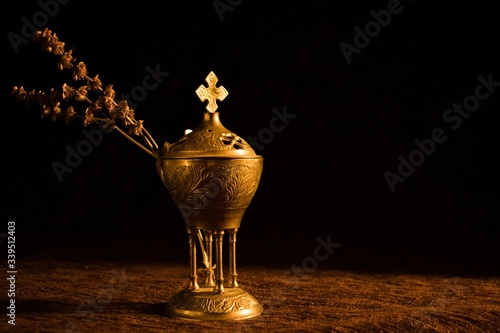 Beautiful church censer with a dried branch with a dark background Fototapeta