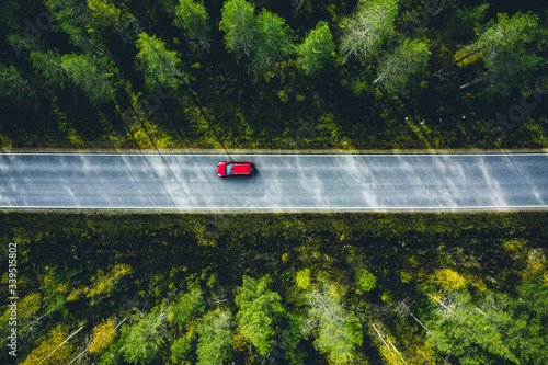 Fotografija Aerial view of red car on a country road in forest in Finland