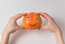 Grapefruit With Funny Face In Female Hands On White Background. Orange With Googly Eyes And Painted Smile