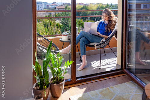 Beautiful young woman working from home on the balcony Wallpaper Mural
