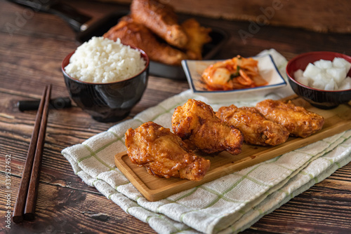 Closed up home made fried chicken with Korean source with garlic, spicy and steamed rice on wooden background, Korean food © Kaojoke