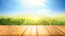 Spring Summer Beautiful Background With Green Juicy Young Grass And Empty Wooden Table In Nature Outdoor. Natural Template Landscape With Blue Sky And Sun.