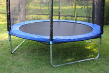 Modern Empty 8ft Trampoline With Outside Pritection Net On Green Grass On A Summer Day Close-up, Fitness Outdoor Training
