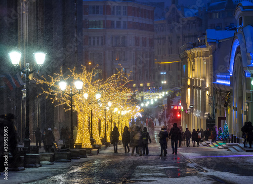 People On Street With Illuminated Trees In City