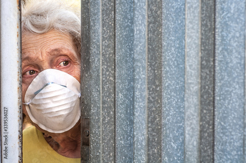 A frightened grandmother in a mask peeps out of the gap in the fence through the gate of her house Canvas Print