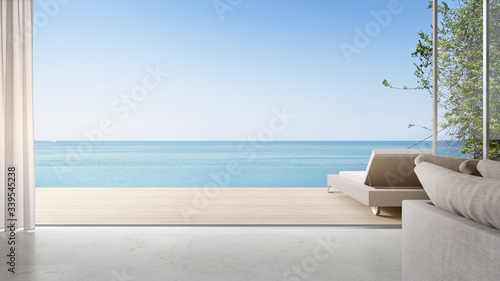 Fototapeta Lounge chair on terrace near bright living room and sofa in modern beach house or luxury pool villa. Cozy home interior 3d rendering with sea view. obraz