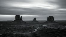 Scenic View Of Monument Valley Against Cloudy Sky At Dusk