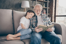 Photo Of Old Grandpa Little Pretty Granddaughter Sit Sofa Hugging Stay House Quarantine Safety Read Interesting Book Fairy Tale Modern Interior Living Room Indoors