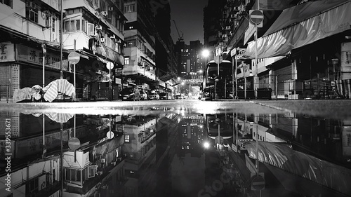 Photo Reflection In Puddle On Street Amidst Buildings At Night