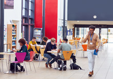 Communal Area Of Busy College Campus With Students Working At Tables And Tutor On Phone