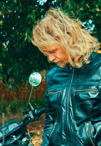 Photo Young handsome guy with a motorcycle, blond with long hair