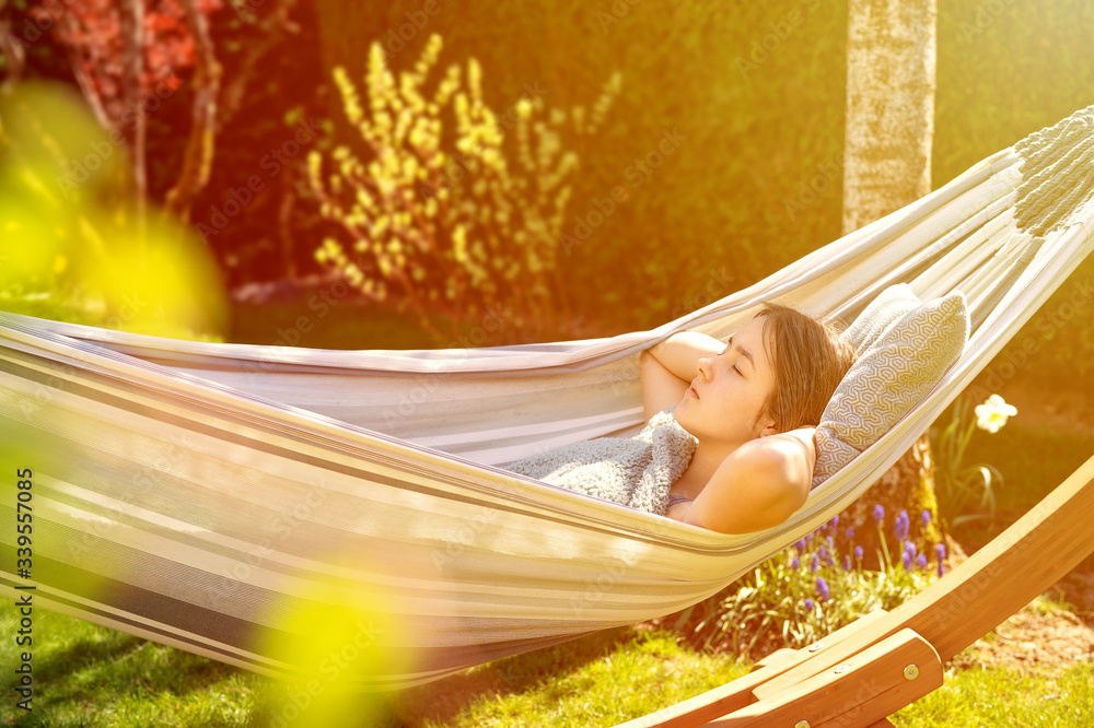 Fototapeta Young girl relaxing having nap in hammock in garden at home at sunset. Slow living, gadget detox and weekend leisure activity. Quarantine and self isolation period
