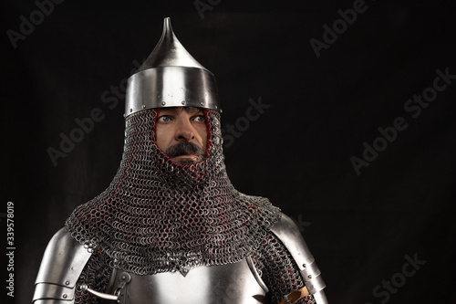 Mannequin man with a beard in a helmet and armor of a knight posing on a black b Canvas Print