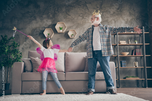 Fototapeta Full length photo of aged old grandpa little pretty granddaughter acting fairy costumes good mood holding hands dancing stay house quarantine safety modern interior living room indoors obraz