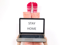 Stay Home Written On Laptop Screen. Legs Up In Pink Socks On The White Background