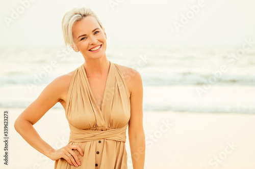 happy middle aged woman elegant looking and feeling confident on beach Fototapet