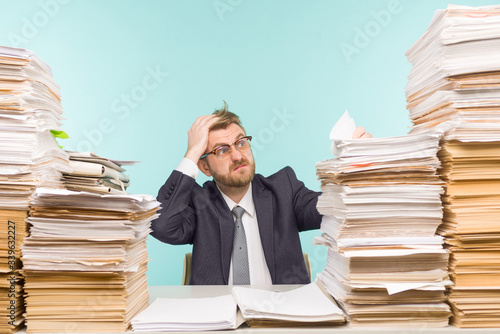 Shocked businessman sitting at the table with many papers in office Fototapeta