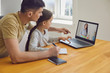canvas print picture - Online learning lessons education school. Father and daughter are doing online education with a teacher using a laptop sitting at home.