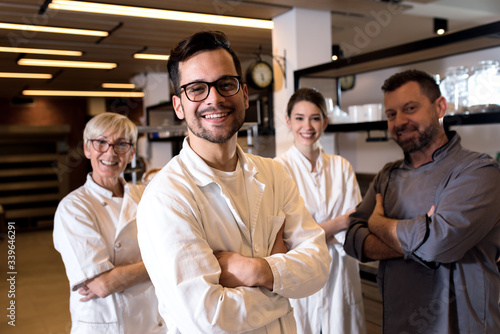 Obraz na plátně Portrait of young male baker at bakery with his colleagues in backgrounds