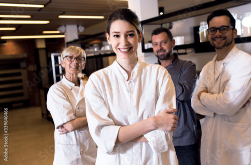 Portrait of young female baker at bakery with her colleagues in backgrounds Canvas-taulu