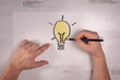 real hands drawing cartoonish doodle of a light bulb