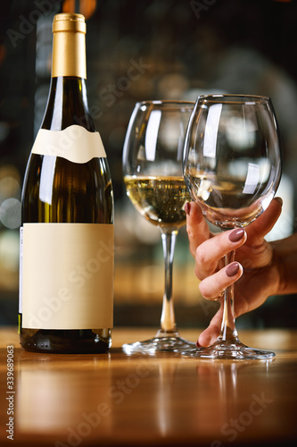 A bottle of wine and glasses on the table, against the background of a wine shakafa Fototapeta