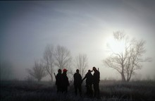 Hunters Standing On Grassy Field Against Sky During Sunrise In Foggy Weather