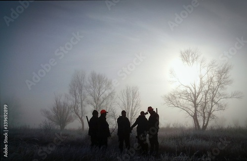Canvas Print Hunters Standing On Grassy Field Against Sky During Sunrise In Foggy Weather