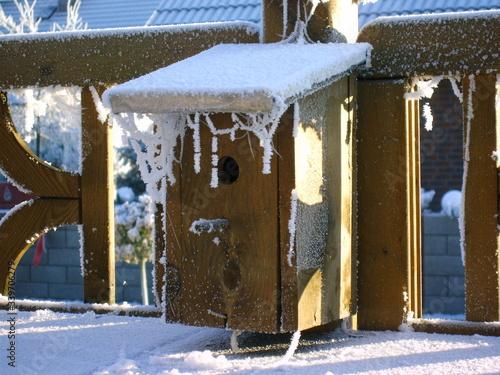 Obraz na plátně Snow Covered Birdhouse On Fence During Winter