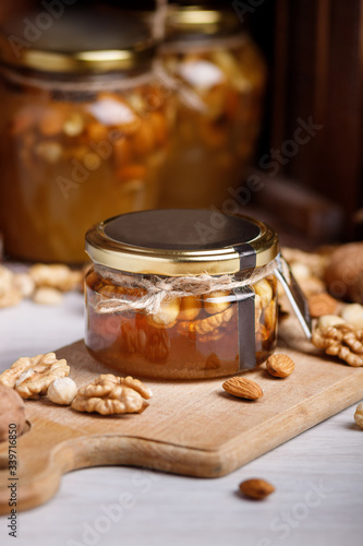 Jar of honey on a wooden board. Honey with nuts.