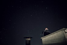 Low Angle View Of Person Sitting On Retaining Wall Against Star Field At Night