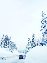 Scenic View Of Car Driving Through Snow Covered Landscape Against Cloudy Sky