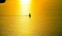 Silhouette Sailboat Sailing In Sea During Sunset