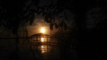Silhouette Gazebo On Pier In Lake At Sunset