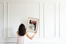 Woman Hanging A Frame On A Whi...