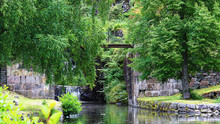 Canal Amidst Trees By Stone Wall