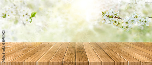Fototapeta Spring background with white blossoms and sunbeams in front of a wooden table. Spring apple garden on the background obraz