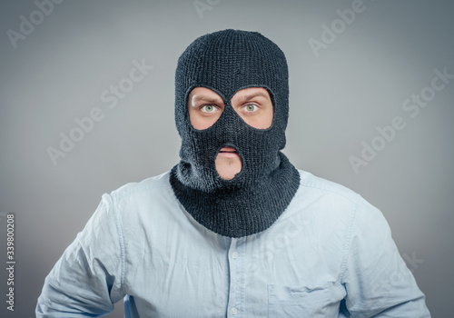 Photo Face of a angry burglar wearing a black ski mask or balaclava
