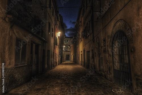 Fototapeta Empty Walkway Amidst Buildings At Night