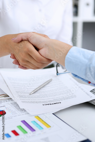 Partnership agreement closeup with man in suit shake hand as hello in background Wallpaper Mural