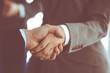 Business people shaking hands while standing with colleagues after meeting or negotiation, close-up. Group of unknown businessmen and women in modern office. Teamwork, partnership and handshake