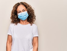 Middle Age Woman Wearing Coronavirus Protection Mask For Covid-19 Epidemic Virus With A Happy And Cool Smile On Face. Lucky Person.