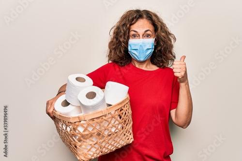 Photo Middle age woman wearing coronavirus protection mask holding big amount of toile