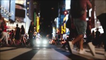 Cinematic Slow Motion Side View Of Many People's Legs Crossing A Busy City Street At Night On Times Square, New York.