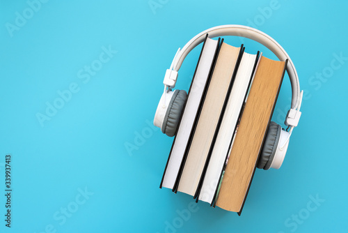 Carta da parati White headphones with stack of books on blue background