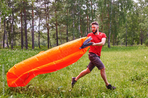 Obraz A young man inflates a lamzac with air. A man inflates an air sofa. on the background of the forest - fototapety do salonu